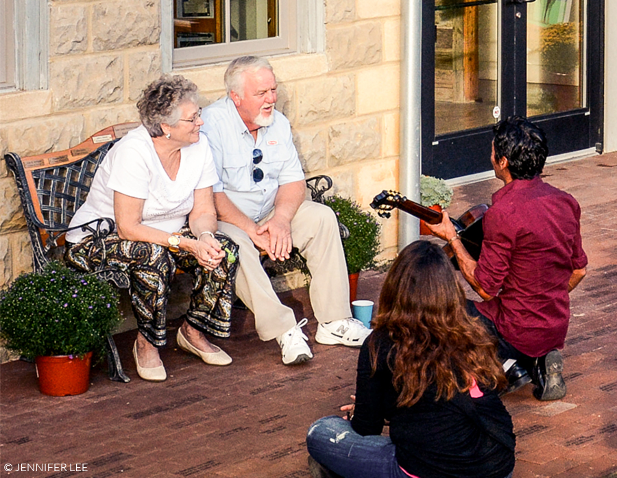 Man Serenading Older Couple with Guitar